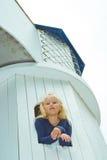 Muchacha que mira hacia fuera la ventana de la torre Imágenes de archivo libres de regalías