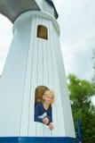 Muchacha que mira hacia fuera la ventana de la torre Fotos de archivo