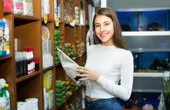 Muchacha que mira la comida seca en tienda del animal doméstico Foto de archivo