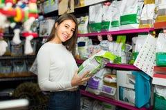 Muchacha que mira la comida seca en tienda del animal doméstico Imagen de archivo libre de regalías