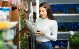 Muchacha que mira la comida seca en tienda del animal doméstico Fotografía de archivo libre de regalías
