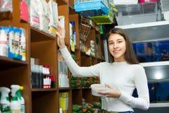 Muchacha que mira la comida seca en tienda del animal doméstico Fotos de archivo libres de regalías