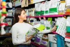 Muchacha que mira la comida seca en tienda del animal doméstico Foto de archivo libre de regalías