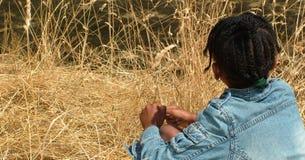 Muchacha que mira la hierba alta Imágenes de archivo libres de regalías