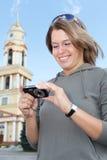Muchacha que mira la pantalla de la cámara compacta Imagen de archivo