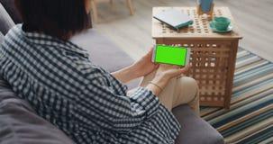 Muchacha que mira la pantalla verde de la maqueta del smartphone que se sienta en el sofá en casa almacen de video