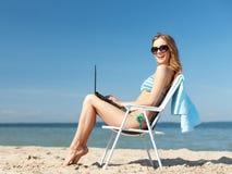 Muchacha que mira la PC de la tableta en la playa Imagen de archivo