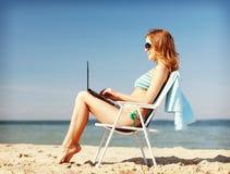 Muchacha que mira la PC de la tableta en la playa Imagen de archivo libre de regalías