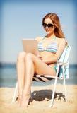 Muchacha que mira la PC de la tableta en la playa Imagenes de archivo