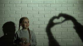 Muchacha que mira la sombra del corazón en la pared y que abraza el oso de peluche, la esperanza y la amabilidad almacen de video