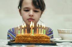 Muchacha que mira la torta de cumpleaños con las velas ardientes Foto de archivo