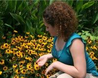 Muchacha que mira las flores Imagen de archivo libre de regalías