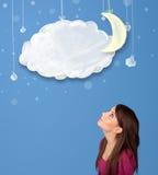 Muchacha que mira las nubes de noche de la historieta con la luna que cuelga abajo Imagenes de archivo