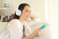 Muchacha que mira lejos que escucha la música en casa Imagenes de archivo