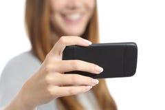 Muchacha que mira los medios vídeos en un teléfono elegante Foto de archivo