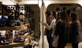 Muchacha que mira los zapatos en una tienda Fotos de archivo
