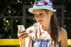 Muchacha que mira móviles imagenes de archivo