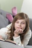 Muchacha que mira para arriba de su libro Imagen de archivo libre de regalías