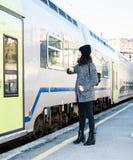 Muchacha que mira para arriba y que se coloca al lado de un tren Imagenes de archivo