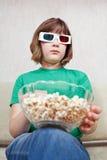 Muchacha que mira películas de la TV en vidrios del estéreo 3D Imagen de archivo