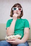 Muchacha que mira películas de la TV en vidrios del estéreo 3D Imagen de archivo libre de regalías