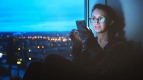 Muchacha que mira Smartphone en fondo de la ciudad
