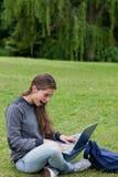 Muchacha que mira su computadora portátil mientras que se sienta en Fotos de archivo