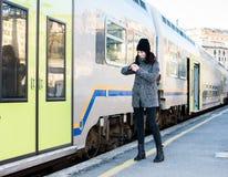 Muchacha que mira su reloj y situación al lado de un tren Fotos de archivo
