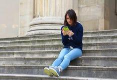 Muchacha que mira su teléfono el sentarse en las escaleras Fotografía de archivo libre de regalías