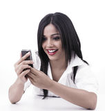 Muchacha que mira su teléfono celular Imagenes de archivo