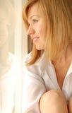 Muchacha que mira a través de la ventana Fotos de archivo