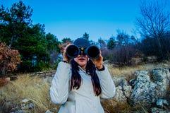 Muchacha que mira a través de los prismáticos en el forst fotos de archivo libres de regalías