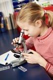 Muchacha que mira a través de un microscopio Foto de archivo libre de regalías