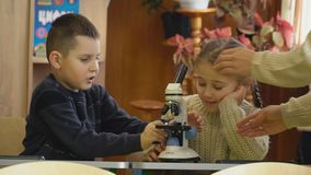 Muchacha que mira a través de un microscopio almacen de metraje de vídeo