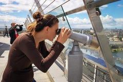 Muchacha que mira a través de un telescopio en el tejado del edificio Fotografía de archivo libre de regalías
