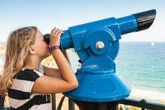 Muchacha que mira a través de un telescopio pagado inmóvil Fotografía de archivo