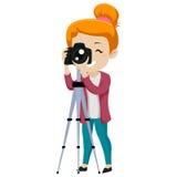 Muchacha que mira a través de una cámara digital en el trípode