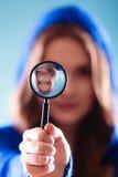 Muchacha que mira a través de una lupa Imagenes de archivo