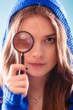 Muchacha que mira a través de una lupa Imagen de archivo libre de regalías