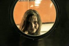 Muchacha que mira a través de una ventana redonda Fotos de archivo libres de regalías