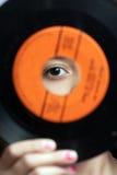 Muchacha que mira a través del agujero en expediente Imagen de archivo