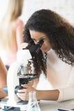 Muchacha que mira a través del microscopio en clase de química Fotografía de archivo libre de regalías