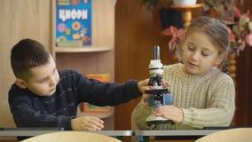 Muchacha que mira a trav?s de un microscopio almacen de metraje de vídeo