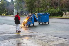 Muchacha que mira un cubo de la basura quemado y derretido del fuego en la ciudad de Atenas después de un acontecimiento de la de fotografía de archivo libre de regalías