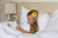 Muchacha que mira una película en una tableta por la mañana en la cama en el dormitorio Imagen de archivo libre de regalías