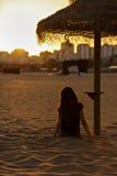 muchacha que mira una puesta del sol la playa Fotos de archivo libres de regalías