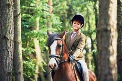 Muchacha que monta un caballo en bosque Fotos de archivo libres de regalías