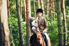 Muchacha que monta un caballo en bosque Fotografía de archivo