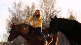 Muchacha que monta un caballo en un rancho Muchacha hermosa de moda que frota ligeramente un caballo Un día de invierno soleado r almacen de metraje de vídeo