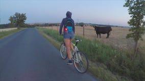 Muchacha que monta una bici en el camino metrajes